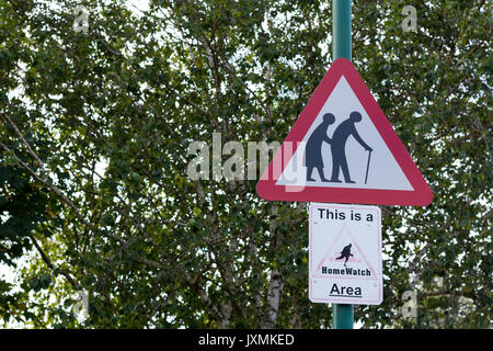 Old people warning red triangular road sign, This is a HomeWatch Area sign, Dorset, UK - Stock Photo