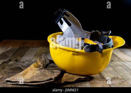 Yellow helmet and welding gloves. Black background and old wooden table. - Stock Photo