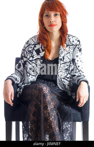 Redhead girl wears black and white jacket and wearing a black skirt. - Stock Photo