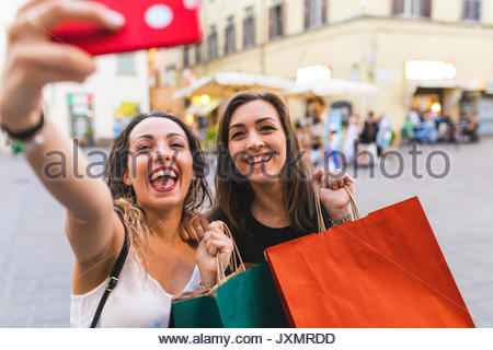 Young women with shopping bags taking selfie smiling