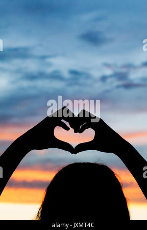 Silhouette of girl making heart with her hands against dramatic sky - Stock Photo