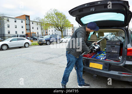 Young man packing fishing rod into boot of car, rear view - Stock Photo