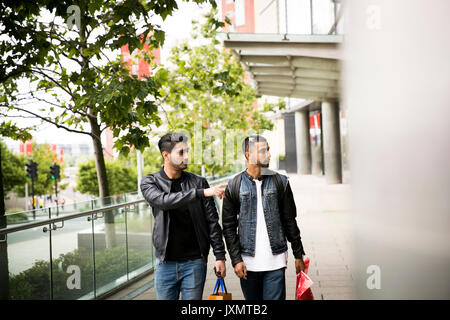 Two young men, walking past shops, pointing in shop window - Stock Photo