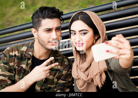 Young man and woman, sitting on park bench, taking selfie with smartphone - Stock Photo