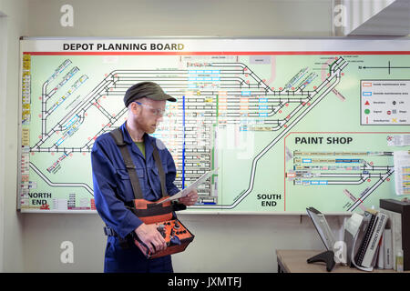 Locomotive engineer with engine shed plans in train works - Stock Photo