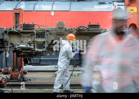Locomotive engineers working on locomotive in train works - Stock Photo
