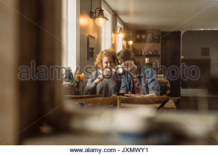 View through cafe window of couple on date smiling - Stock Photo