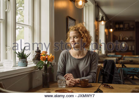 Woman in cafe looking away out of window smiling - Stock Photo