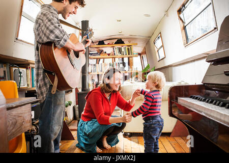 Family with baby boy living on barge playing guitar and dancing - Stock Photo