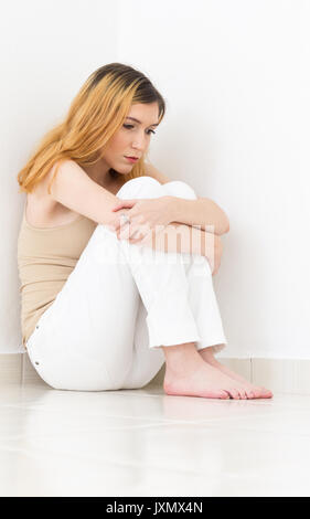 Lonely woman is barefoot and very sad. Feelings of solitude and isolation. She hugs her knees and is looking down. - Stock Photo