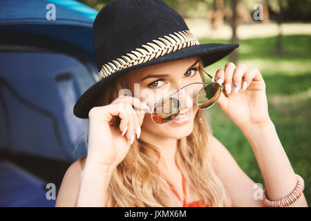 Portrait of young boho woman holding sunglasses at festival - Stock Photo