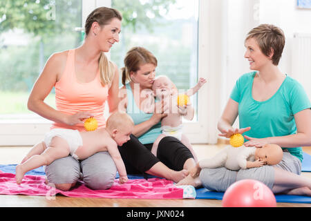 Young women practicing massage for their babies in mother-child  - Stock Photo