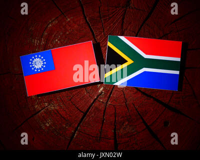 Myanmar flag with South African flag on a tree stump isolated - Stock Photo