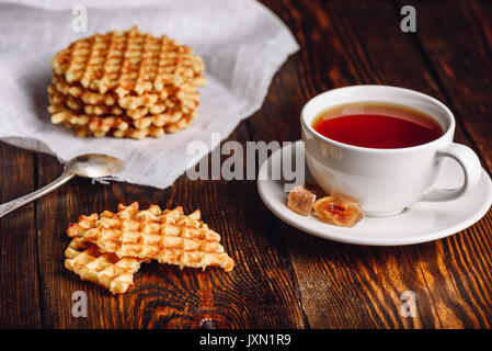 White Cup of Tea with Waffles Stack on Napkin and Pieces of Waffle on Wooden Surface. - Stock Photo