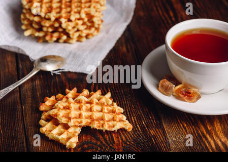 White Cup of Tea with Waffles Stack on Napkin and Pieces of Waffle on Wooden Surface and Spoon. - Stock Photo