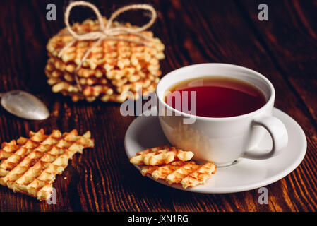 White Cup of Tea with Belgian Waffles Stack and Pieces of Waffle on Wooden Surface. - Stock Photo