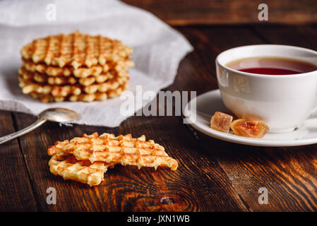 White Cup of Tea with Belgian Waffles Stack on Napkin and Pieces of Waffle on Wooden Surface. - Stock Photo