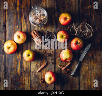 Red Apples with Scattered Clove, Cinnamon and Anise Star. Candy Sugar and Some CLove in a Jar. Ingredients for Prepare - Stock Photo