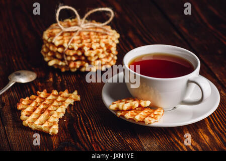 White Cup of Tea with Waffles Stack and Pieces of Waffle on Wooden Surface. - Stock Photo