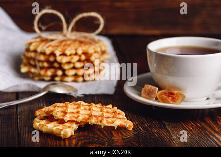 Breakfast with Waffles Stack on Napkin, White Cup of Tea and Pieces of Waffle on Wooden Surface. - Stock Photo