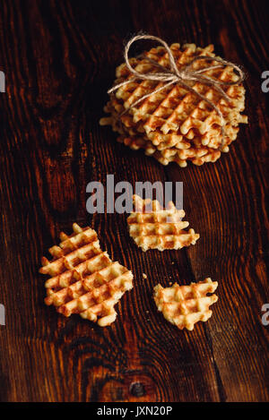 Stack of Waffles and Waffle Pieces on Wooden Surface. Vertical Orientation. - Stock Photo