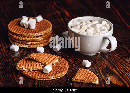 Broken Dutch Waffles with White Cup of Coffee with Marshmallow and Waffle Stack. - Stock Photo