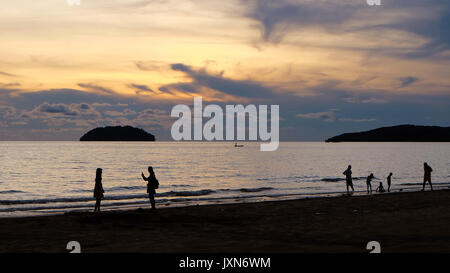 A beach front during sunset, with silhouette of people playing at the beach and enjoying the view. Distant islands - Stock Photo