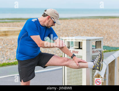 Young man stretching in preparation for doing a morning run. - Stock Photo