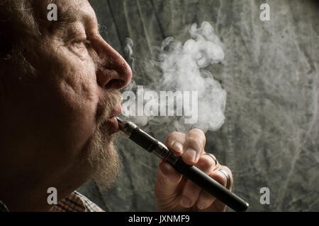 An older man with a beard smoking an electronic cigarette ( vaping an E-cigarette), a healthier option than tobacco - Stock Photo