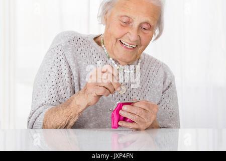 Happy Senior Woman Inserting Coin In Small Purse - Stock Photo