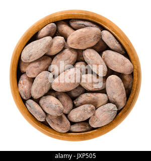 Cocoa beans in wooden bowl. Dried and fully fermented seeds of Theobroma cacao. Brown cacao beans. Aztec gold. Basis - Stock Photo