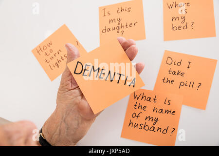 Close-up Of Person's Hand Holding Dementia Sticky Note At Home - Stock Photo