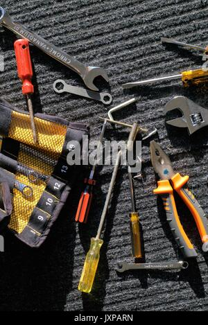 Various mechanic tools on gray-black work mat outdoors in direct sunlight - Stock Photo