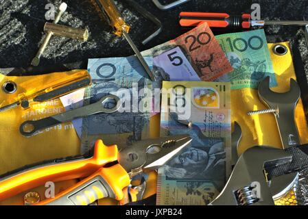 Australian money and tools of mechanic on black mat in direct sunlight - Stock Photo