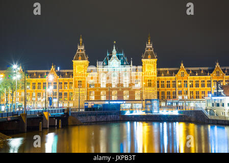 Amsterdam, Netherlands - April 20, 2017: City scenic from Amsterdam in the Netherlands by night with the central - Stock Photo