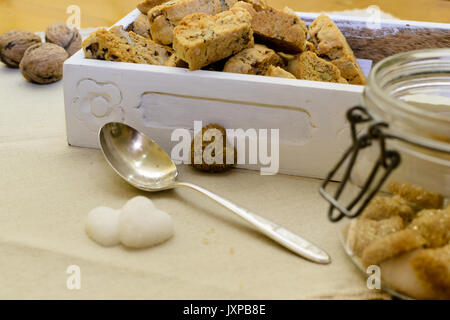 Italian tozzetti in a white wooden box with heart shaped sugar cubes and a silver spoon. Side view. Landscape format. - Stock Photo