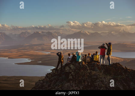 Big group of ten friends on mountain top having rest at sunset time. Space for text - Stock Photo