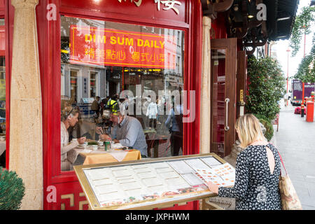Caucasian woman looking at menu outside Chinese restaurant in Chinatown, London, England, UK - Stock Photo