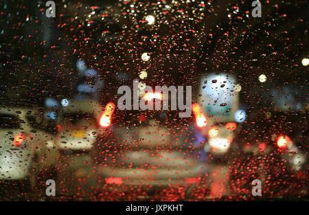 Street and car lights through raindrops on car windscreen ...  Street and car ...