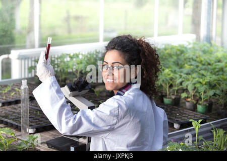 Young woman biologist holding test tube with chemicals in front of microscope and sprouts in greenhouse. Plant protection - Stock Photo