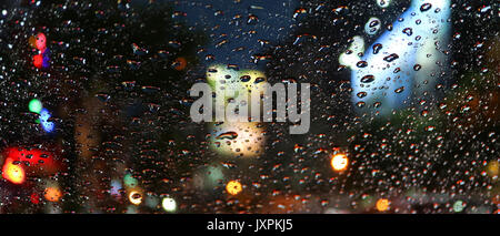 Raindrops on the car windshield during driving on the urban street at night - Stock Photo