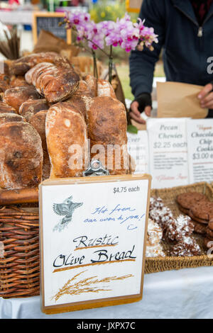Baskets of fresh bread for sale on display at a farmers market. Baguettes and rustic olive bread. Location: Oakland, - Stock Photo