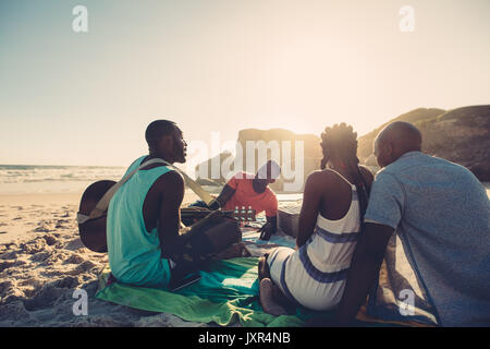 African young man singing and playing guitar on the beach. Group of four people having great time at the beach picnic. - Stock Photo
