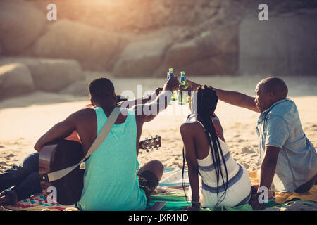 Young people toasting with beer bottles while sitting on beach. Group of friends having drinks together. - Stock Photo