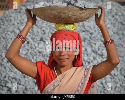 Closeup street portrait of a sari-clad mature Indian Adivasi tribal woman, carrying on her head a metal bowl with - Stock Photo