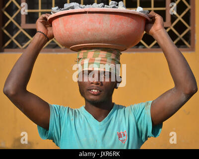 Closeup street portrait of a young Indian Adivasi tribal man, carrying on his head a plastic bowl with crushed rocks - Stock Photo