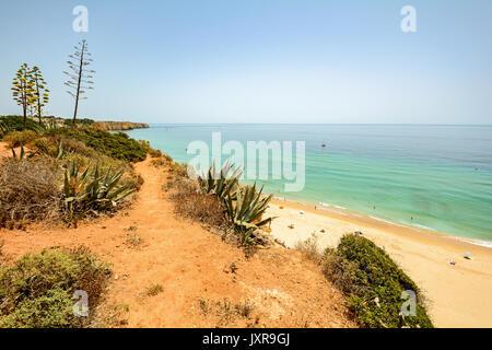 View from the cliffs to busy beach Praia do Porto de Mos near Ponta da Piedade, Lagos Algarve Portugal - Stock Photo