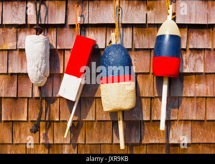 Vintage fishing buoys hanging on a wood shingle wall. Red, white and blue - Stock Photo