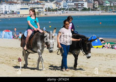 Weymouth, Dorset, UK. 17th Aug, 2017. UK Weather. Children having a donkey ride on the beach during the warm sunny - Stock Photo