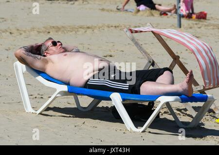 Weymouth, Dorset, UK. 17th Aug, 2017. UK Weather. A sunbathers on the beach enjoying the warm sunny weather at the - Stock Photo